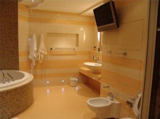 Облицовка стен в помещении ванной комнаты при помощи плитки и агломерата